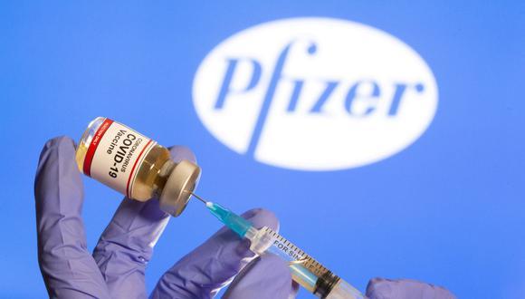 """Una mujer sostiene una pequeña botella etiquetada con una etiqueta de """"Vacuna contra el coronavirus COVID-19"""" y una jeringa médica frente al logotipo de Pfizer. (REUTERS / Dado Ruvic)."""