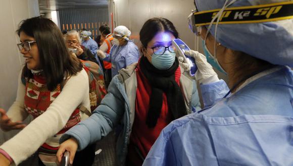El personal médico verifica la temperatura de las personas en medio de la pandemia por el COVID-19 (Foto: Luka Gonzales / AFP)
