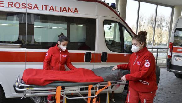 Miembros de la Cruz Roja Italiana con máscaras faciales paran junto a una camilla vacía frente al Hospital Cívico Codogno en Lodi, norte de Italia. (Foto: EFE).