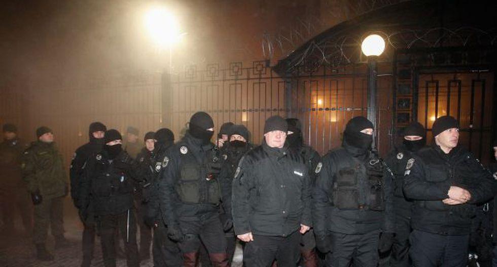 Los policías ucranianos protegen el edificio de la embajada rusa con humo detrás durante el mitin de activistas ucranianos en Kiev, Ucrania. (Foto: EFE)