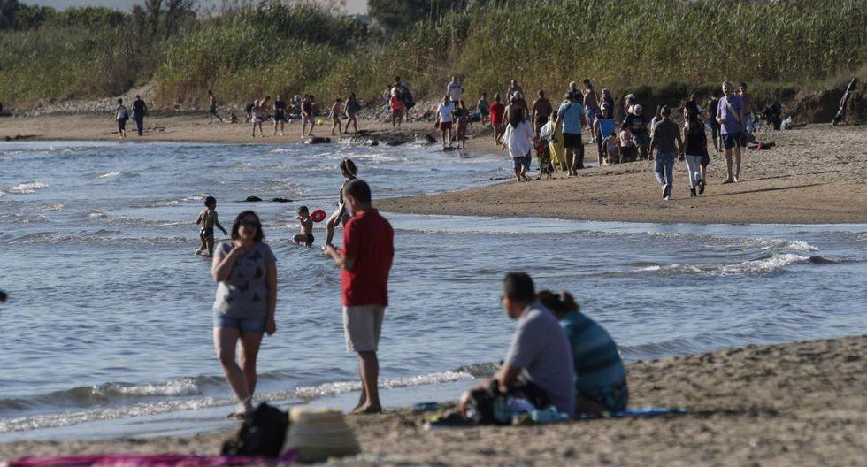 """""""Estaba tan emocionada, extrañaba tanto el mar. Respirar un poco de yodo, poner los pies en la arena, en el agua, comer un plato de espaguetis. Es más que suficiente para mí"""", comenta sonriente Arianna Tucci, residente de Roma. Imagen de la playa de Ladispoli. (EFE/EPA/GIUSEPPE LAMI)."""