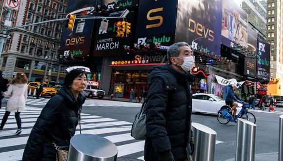 Una pareja de turistas pasean por las calles de Nueva York. El hombre muestra una mascarilla como medida de protección ante el coronavirus. Foto: Reuters