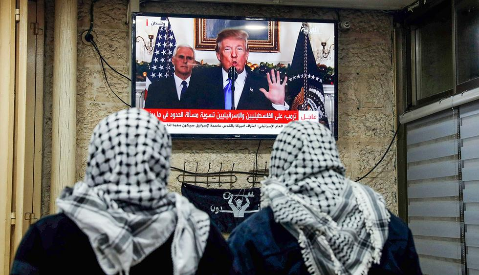A picture taken on December 6, 2017 shows Palestinian men watching an address given by US President Donald Trump at a cafe in Jerusalem.  / AFP / Ahmad GHARABLI