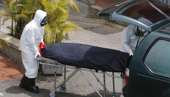 Personal funerario sube a un vehículo el cuerpo de una víctima de coronavirus covid-19 en el Hospital General de Medellín, Colombia. (EFE/ Luis Eduardo Noriega A.).