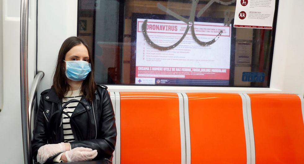 Una mujer que lleva máscara protectora se sienta en un tren subterráneo donde se obliga a los pasajeros a mantener la distancia social. (REUTERS / Remo Casilli).