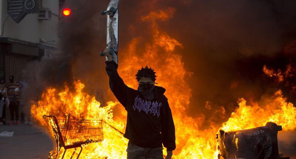 Las manifestaciones por la muerte del afroamericano George Floy a manos de un policía se han extendido a todo Estados Unidos. Esta imagen del 30 de mayo muestra a un manifestante parado frente a un incendio durante una protesta en Los Ángeles. (Foto: AP / Ringo H.W. Chiu)