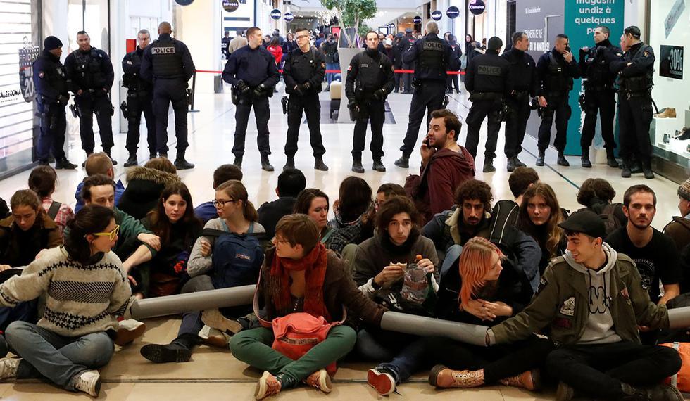 Los activistas se sientan frente a la policía francesa mientras bloquean un pasillo del centro comercial Westfield Les 4 Temps, cerca de París. (Foto: Reuters)