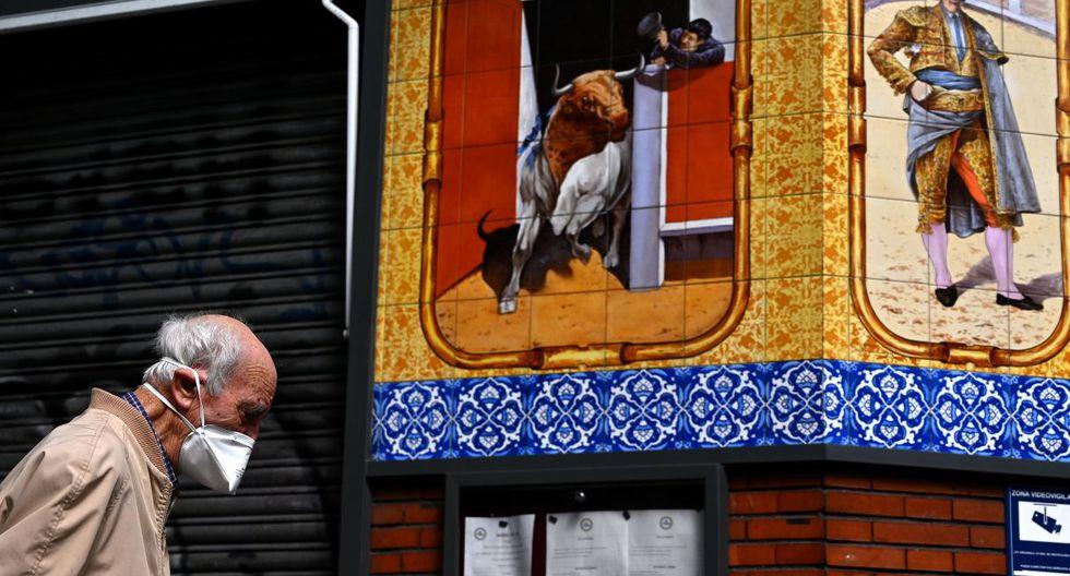 Un anciano, que usa una mascarilla como protección, pasa frente a un restaurante cerrado en Madrid, España. (Gabriel BOUYS / AFP).