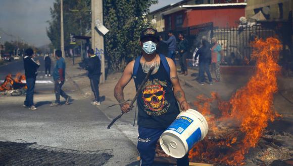 La gente protesta en medio de barricadas en llamas en demanda de ayuda económica del gobierno de Chile para hacer frente a la pandemia de coronavirus. (Foto de RAMON MONROY / AFP).