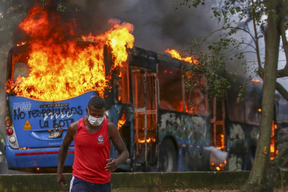 Un hombre corre cerca de un autobús de transporte público en llamas durante una protesta contra un proyecto de reforma tributaria lanzado por el presidente colombiano Iván Duque, en Cali. (Foto de Paola MAFLA / AFP).