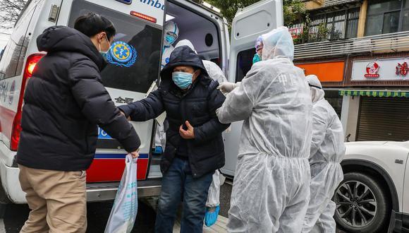 La imagen muestra a una persona sospechosa de portar el coronavirus siendo trasladada por trabajadores de salud en China. (Foto: AFP)