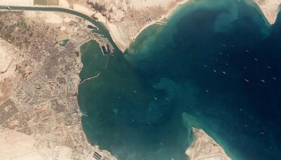 En la esquina superior izquierda se observa al Ever Given atascado. En el lago a la derecha, decenas de barcos que esperan que se libere la vía para pasar. (Reuters).