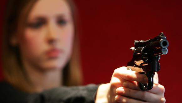 Imagen referencial en la que se ve a una mujer sosteniendo un revolver Magnum Colt Python .357. AFP