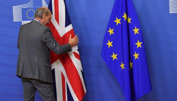 Un funcionario coloca una bandera británica junto a una bandera de la UE antes de una reunión entre la primera ministra británica Theresa May y el presidente de la Comisión Europea Jean-Claude Juncker. (AFP).