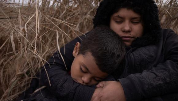 Jennifer, una migrante en busca de asilo de Honduras, sostiene a su hijo Carlos de seis años, mientras se refugian con solicitantes de asilo junto al campo después de cruzar el río Grande hacia los Estados Unidos desde México en una balsa en La Joya, Texas. (Foto: REUTERS / Adrees Latif).