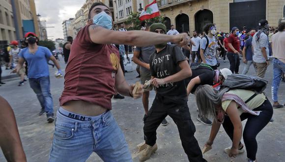 Manifestantes arrojan piedras contra la policía de Líbano durante una protesta en Beirut. (Foto: JOSEPH EID / AFP).