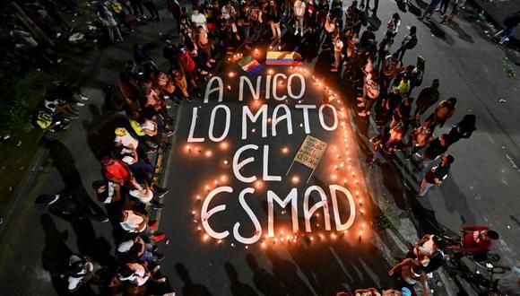 Familiares y amigos de Nicolás Guerrero, quien fue asesinado durante enfrentamientos con la policía antidisturbios de Colombia en una protesta, se reúnen alrededor de velas en una vigilia. (Foto de Luis ROBAYO / AFP).