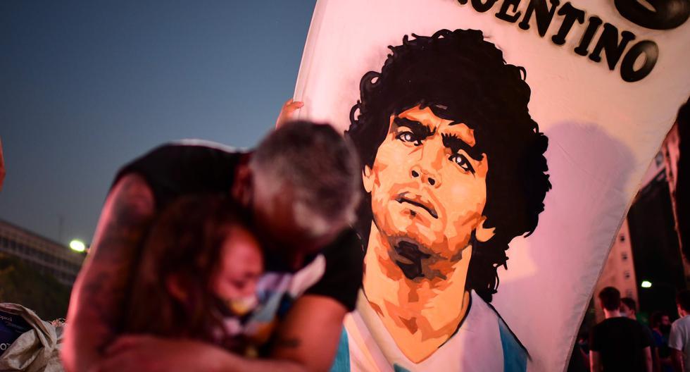 Un hombre y su hija en el Obelisco de Buenos Aires llorando a Diego Armando Maradona el día en que falleció. (AFP)