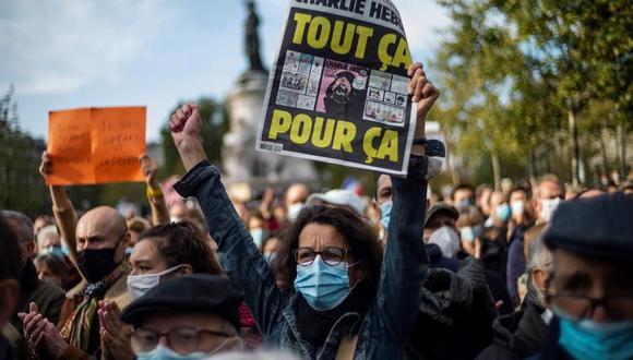 Una mujer sostiene la controvertida portada del semanario satírico Charlie Hebdo que muestra las caricaturas del profeta Mahoma mientras la gente se reúne en la Place de la Republique para una manifestación contra el terrorismo. (EFE / EPA / YOAN VALAT).