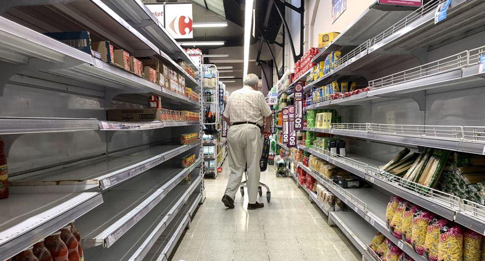 """Un hombre camina junto a los estantes vacíos de un supermercado, como resultado de las compras de cuarentena debido al coronavirus, en Buenos Aires. Argentina prohibió la entrada al país a personas que en los últimos 14 días hayan pasado por """"zonas de riesgo"""". (Foto: AFP)."""