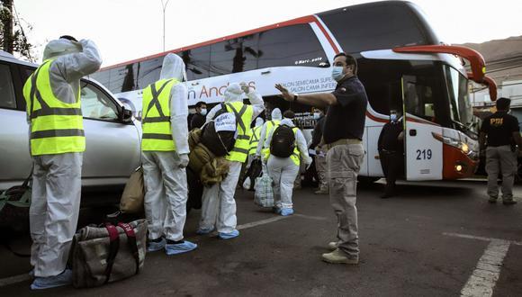Migrantes venezolanos suben a un autobús rumbo al aeropuerto para ser deportados de Chile, el 25 de abril de 2021. (Foto referencial, IGNACIO MUNOZ / AFP)..