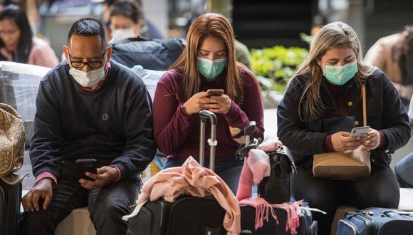 Unos pasajeros usan mascarillas para protegerse contra la propagación del Coronavirus cuando llegan en un vuelo desde Asia al Aeropuerto Internacional de Los Ángeles, California. (Foto: Archivo/AFP).