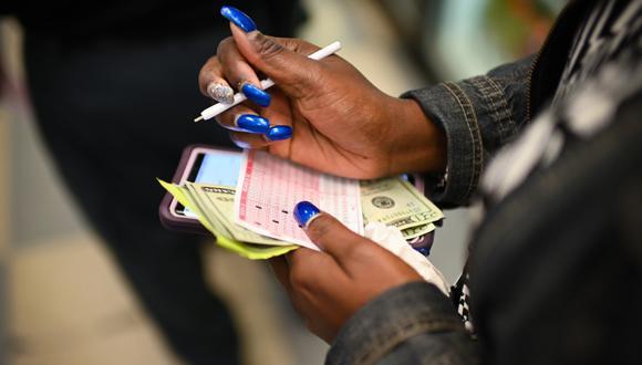 Imagen referencial. Los colombianos robaron casi de US$ 200.000 a las abuelas hispanas en el sur de California (Estados Unidos). Una mujer compra un boleto para el sorteo del premio mayor. (Eric BARADAT / AFP).