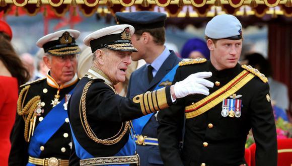 En esta foto de archivo tomada el 3 de junio de 2012, el Príncipe Felipe está junto al Príncipe Harry durante el Thames Diamond Jubilee Pageant en el río Támesis en Londres. (Foto de JOHN STILLWELL / POOL / AFP).