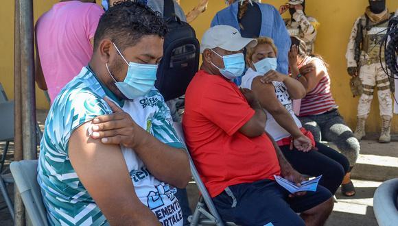Varias personas migrantes reposan tras ser vacunados contra el COVID-19 hoy, en Tijuana, estado de Baja California (México). (Foto: EFE/ Joebeth Terriquez)