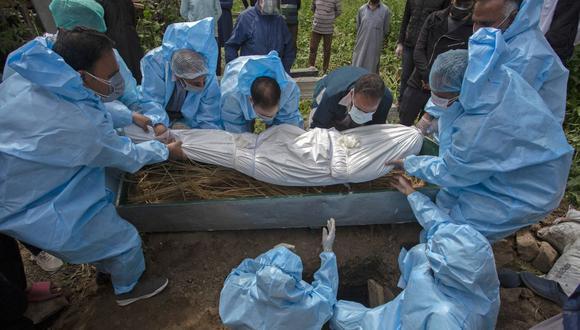 Personal con equipo de protección entierra a una víctima de coronavirus Covid-19 durante un funeral en Srinagar, India, el 7 de mayo de 2021 (Foto de Abid Bhat / AFP)..
