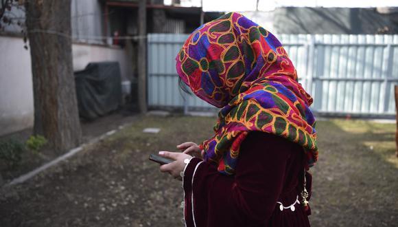 En esta foto tomada el 19 de enero de 2021, una periodista afgana, que huyó de su casa en el centro de Afganistán, usa un teléfono móvil después de una entrevista con AFP en Kabul. (WAKIL KOHSAR / AFP).