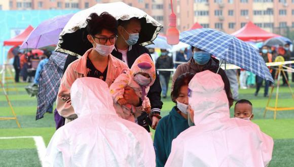 La gente se alinea bajo la lluvia para hacerse la prueba del coronavirus COVID-19 como parte de un programa de pruebas masivas luego de un nuevo brote en Qingdao, en la provincia oriental de Shandong. (Foto: AFP / STR AND STR).