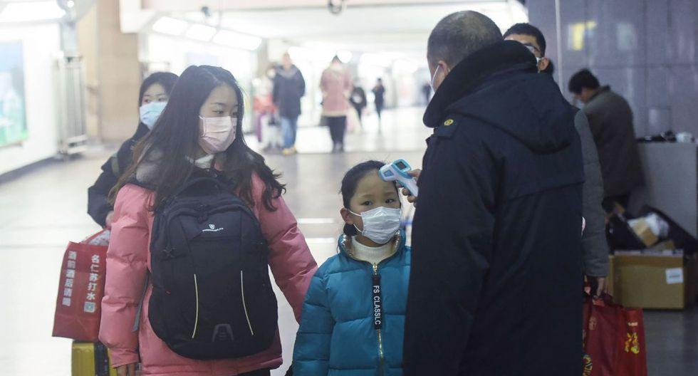 Un miembro del personal (R) verifica la temperatura corporal de un niño después de que un tren de Wuhan llegara a la estación de trenes de Hangzhou. (Foto: AFP)