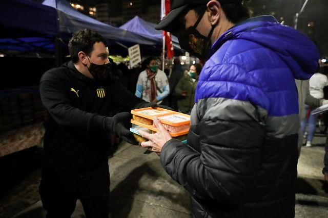 En la imagen, un hombre recibe alimentos durante una olla popular en Montevideo. Muchas de las personas que se quedaron sin empleo a causa de la pandemia han recibido subsidios estatales. (EFE)