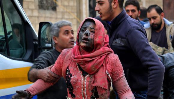 En esta foto de archivo tomada el 15 de febrero de 2019, hombres sirios ayudan a una mujer herida cubierta de polvo luego de un ataque en la ciudad de Khan Shaykhun, en la provincia de Idlib. (Foto de Anas AL-DYAB / AFP).