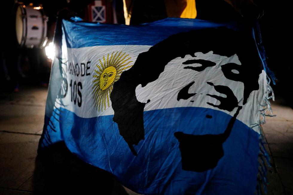 Un aficionado al fútbol sostiene una bandera argentina con el rostro del fallecido leyenda del fútbol argentino Diego Armando Maradona pintado durante un homenaje a él el día después de su muerte. (REUTERS/Nacho Doce).
