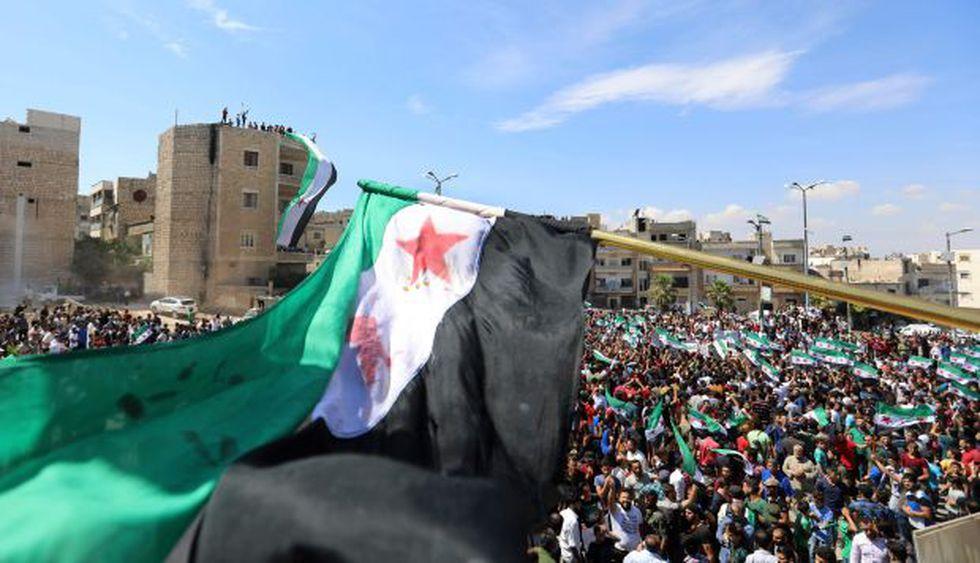 Manifestantes sirios agitan la bandera de la oposición mientras protestan contra el régimen y su aliado Rusia, en la ciudad de Idlib, controlada por los rebeldes. (Foto: AFP)
