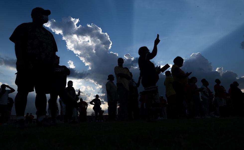 Un grupo de personas presentan sus respetos a George Floyd durante una vigilia a la luz de las velas en la escuela secundaria Jack Yates, en Houston, Texas, lugar donde creció. (Foto por ANDREW CABALLERO-REYNOLDS / AFP)