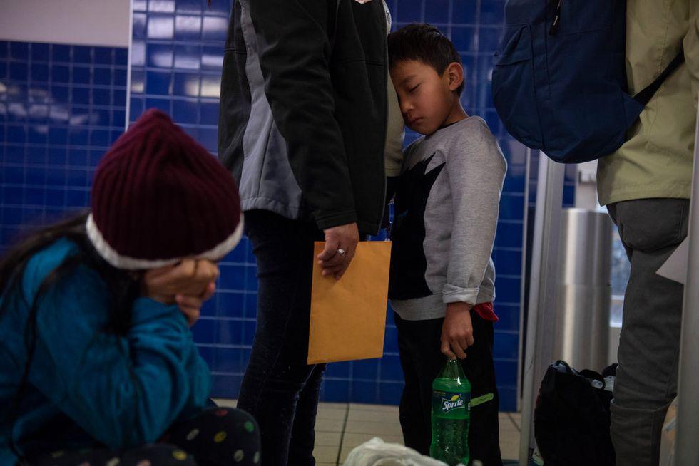 Un niño se aferraba a su madre mientras esperaban en una fila de solicitantes de asilo en una estación de autobuses en San Antonio. (Callaghan O'Hare para The New York Times).