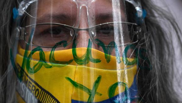 """Una enfermera lleva una mascarilla del color de la bandera venezolana y una careta que dice """"Vacunas ya"""" durante una protesta en Caracas, el 17 de abril. 2021.  (Federico PARRA / AFP)."""