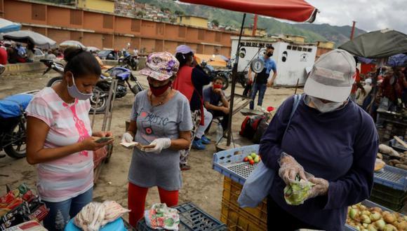 Personas hacen compras en el Mercado Mayorista de Coche en Caracas. Las mascarillas al cuello, a modo de pañuelo, se han convertido en tendencia en Caracas, epicentro de la COVID-19 en Venezuela. (Foto: EFE/RAYNER PEÑA R.).