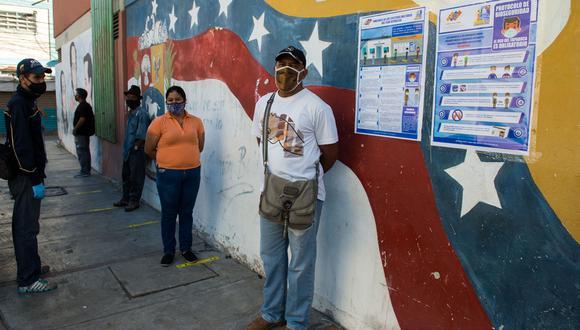 Los votantes hacen cola acatando las medidas de distanciamiento sanitario en un colegio de Caracas, Venezuela. (Foto de Cristian Hernandez / AFP).