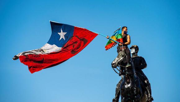 Un manifestante agita banderas chilena y mapuche desde lo alto del monumento al General Baquedano en la Plaza Italia el 9 de octubre de 2020. (Martín BERNETTI / AFP).