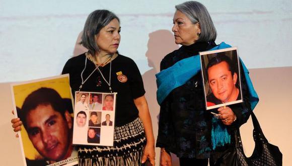 Rosario Villanueva y Yolanda Moran muestran fotos de sus hijos desaparecidos en el 2009 y 2008, respectivamente. Ellas asistieron a la presentación del informe sobre la masacre de Allende perpetrada por Los Zetas. (AFP).