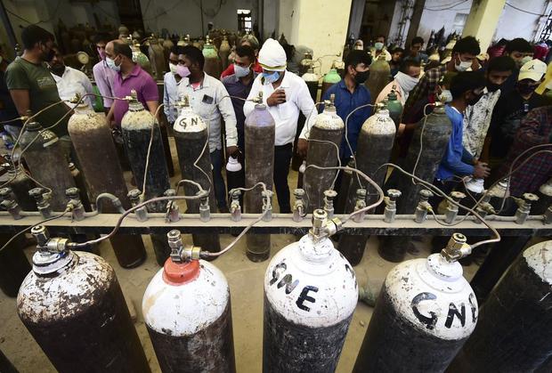 Las personas rellenan cilindros de oxígeno médico para pacientes con coronavirus Covid-19 en una estación de recarga en Allahabad el 20 de abril de 2021. (Foto de SANJAY KANOJIA / AFP).