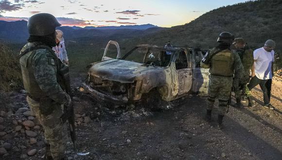 Fuerzas del orden rodean el auto quemando donde nueve miembros de la familia LeBarón fueron asesinados y quemados durante una emboscada en Bavispe, Sonora. (Archivo / AFP)