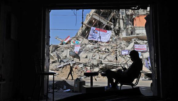 Un hombre se sienta cerca de un edificio destruido en los recientes ataques aéreos israelíes en la ciudad de Gaza. (Foto de MOHAMMED ABED / AFP).