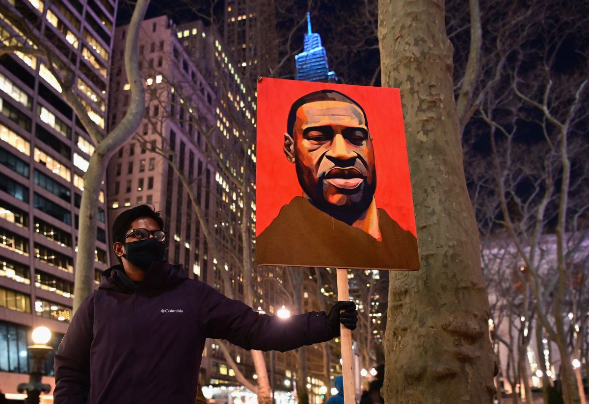 A protester holds a banner with a photo of George Floyd on the first day of former police officer Derek Chauvin's trial. (Photo by Angela Weiss / AFP).