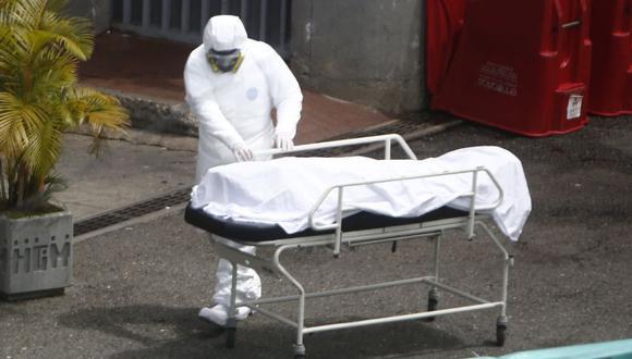 Personal sanitario transporta el cuerpo de una víctima de coronavirus en Medellín, Colombia. (EFE/ Luis Eduardo Noriega A.).