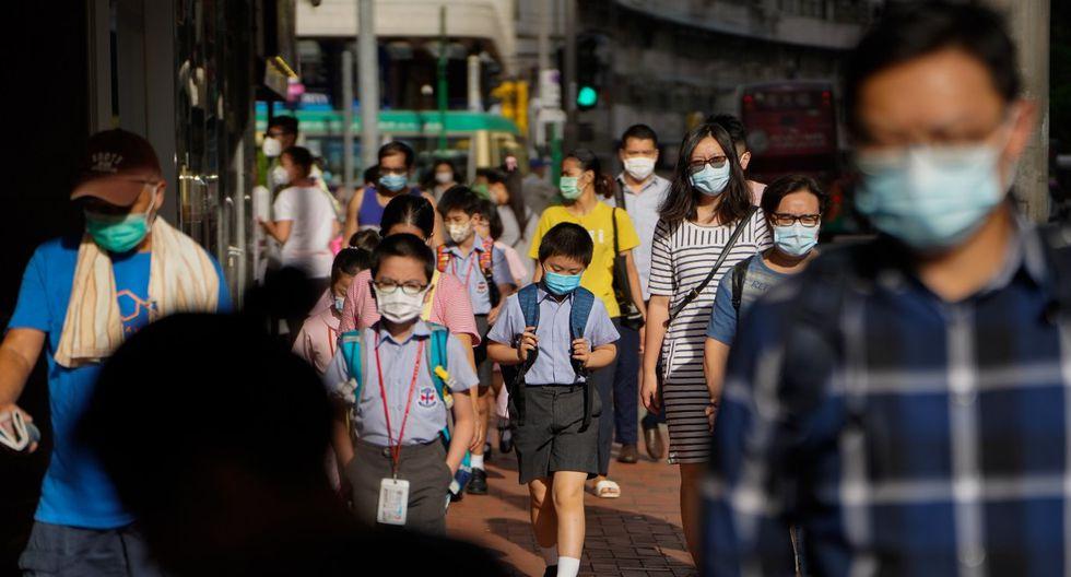 Imagen referencial. Los peatones y escolares con máscaras protectoras caminan por una acera en Hong Kong. (Roy Liu/Bloomberg).